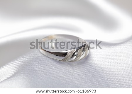 Close up photo of platinum or silver ring on white textile