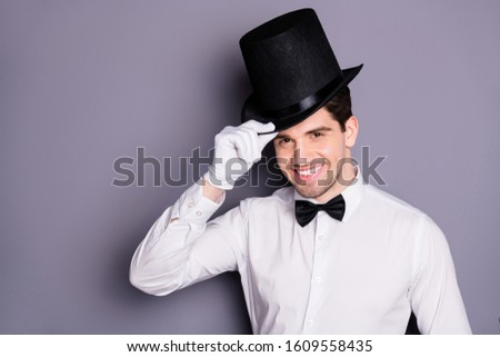 Close up photo of positive cheerful magician man ready entertain audience touch hands black hat isolated over grey color background