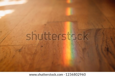 Close up photo of rainbow on wooden floor.