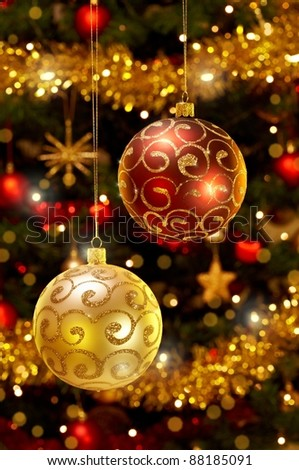 Close-up photo of red and gold christmas baubles hanging on christmas tree.?