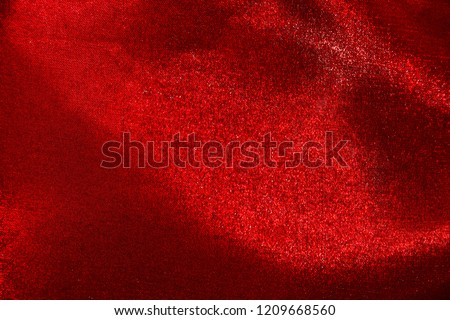 Close up photo of red shimmering slightly uneven fabric for your vivid textured background.