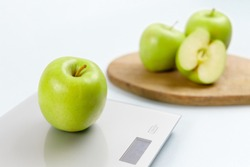 Close up photo of ripe green apple on gray digital kitchen scales. On the background several apples on wooden board. Healthy eating habits. Weighing products. Healthy food and diet concept.