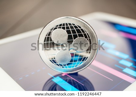 close-up photo of ripple cryptocurrency physical coin on the tablet computer showing stock market charts. trading ripple cryptocoin concept on the wooden table - Shutterstock ID 1192246447