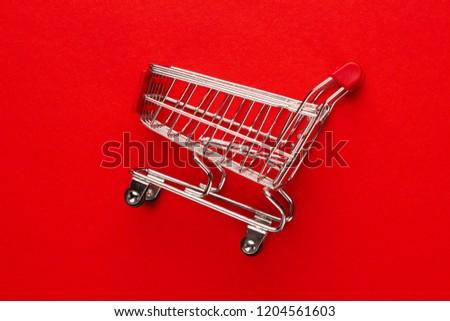 close-up photo of shopping trolley on red background. minimalistic photo of pushcart