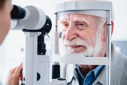 Close up photo of smiling senior male patient during sight examination