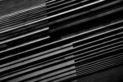 Close-up photo of structural wall of modern building. Abstract futuristic hi-tech architecture. Geometric background with linear pattern, panels, stripes and parallel lines in diagonal composition.