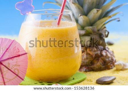 Close up photo of summer cocktail - mixed pineapple drink on a sand and blue background.