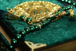 Close up Photo of Tasbih Muslim prayer beads in glossy Golden and green colour.