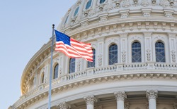 Close up photo of the Capitol Building Rotunda in Washington, D.C. with the American Flag flying proudly with a blue sky.