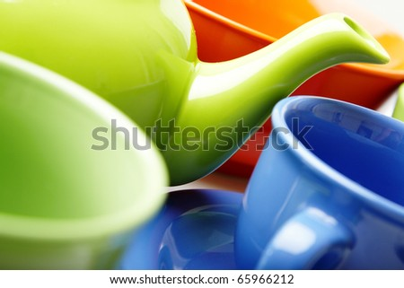 Close-up photo of the fragment of tea service consisting of teapot and cups. Natural color. Shallow depth of field added by the lens for natural view