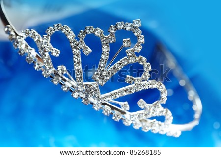 Close-up photo of the silver diadem with diamonds on a blue background with bokeh