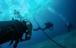 Close up photo of three divers swimming after each other close to anchor chain in blue water. Light at surface, air bubbles from underwater breathing. Tropical Scuba Sea Divers