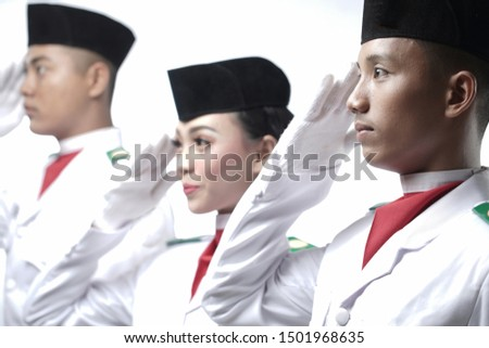 Close up photo of Three Indonesian National Flag Hoisting Troop salutes isolated in white. National Paskibraka Council