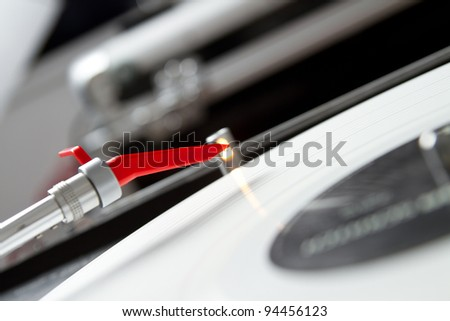 Close up photo of tonearm above white vinyl record - stock photo