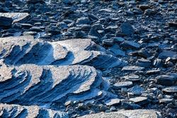 Close up photo of tough and sharp rocky beach of sedimentary rocks
