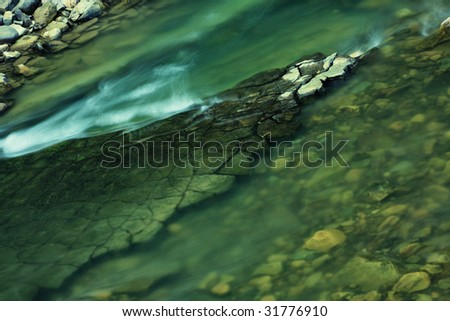 Close-up photo of transparent mountain stream in deep green tones