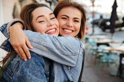 Close-up photo of two attractive happy woman friends hugging each other on city street, looking at camera
