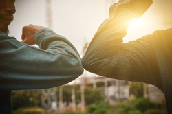 Close-up photo of two people hitting their elbows to avoid the outdoor coronavirus. Friends demonstrated a new way of greeting during healthcare concept. Spacing between people.