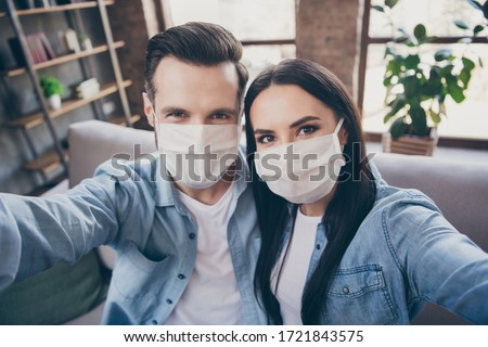 Close up photo of two people spouses make selfie blogging healthcare cov infection epidemic protection sit comfort couch wear medical mask in house indoors
