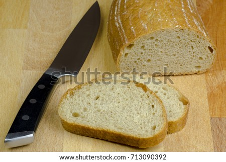 Close-up photo of two slices of bread cut by knife with black handle on a wooden board table with blurred background #713090392