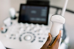 Close up photo of ultrasound scanner in the hands of female African American doctor. Diagnostics. Sonography. Modern ultrasound machine on the blurred background