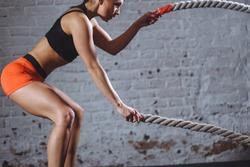 close up photo of woman doing Battle rope workout near white brick wall