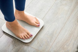 Close-up photo of woman legs stepping on floor scales indoors, space for text. Overweight problem
