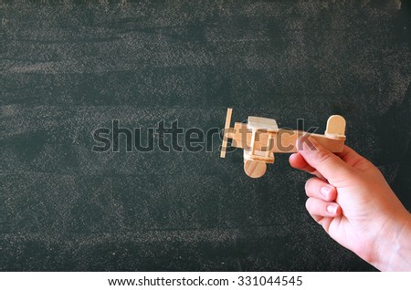 close up photo of woman's hand holding wooden toy airplane against chalkboard .  inspiration concept  #331044545