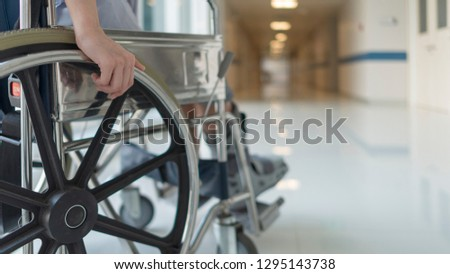 Close up photo of woman sitting on the wheel chair in hospital walk way. De focus picture.Her hand controlling the wheel.Right leg was wearing the orthopedic boots after fracture of foot.