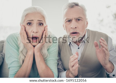 Close up photo of worried grandmother grandfather impressed watch film scream shout dressed teal brown pullover in apartment ストックフォト ©