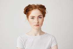 Close up photo of young beautiful ginger girl with buns looking at camera over white background.