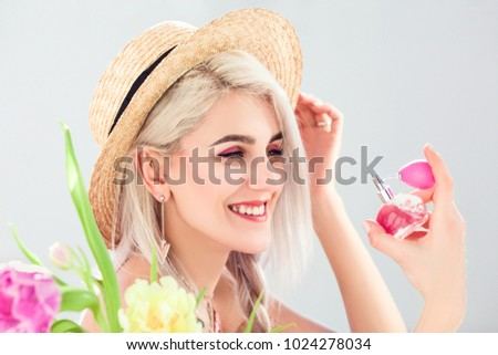Close up photo of young beautiful happy smiling girl holding, using perfume in pink bottle. Model wearing straw hat, posing near spring flowers, on white background.