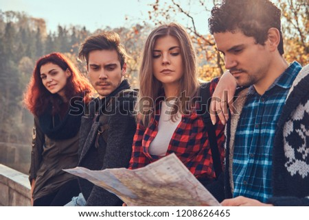 Close-up photo of young friends looking at map and planning trip in autumn forest. #1208626465