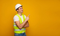 Close up photo of young happy and confident foreman or architect in build helmet is posing isolated on yellow background.