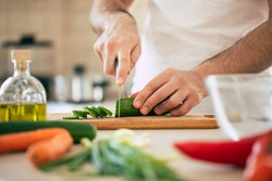 Close up photo of young male hands is preparing wonderful fresh vegan salad in the kitchen at home