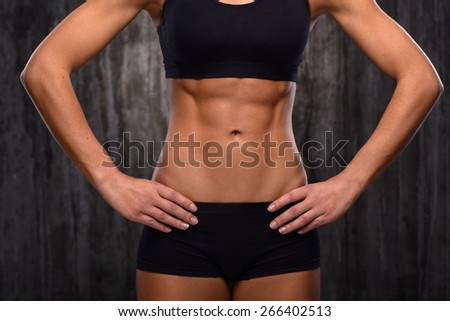 Close up photo of young mixed race sporty woman. She demonstrating her biceps and slim belly. Fitness concept