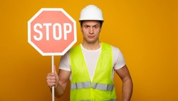 Close up photo of young serious and confident foreman or architect in build helmet with stop sign in hand is posing isolated on yellow background.