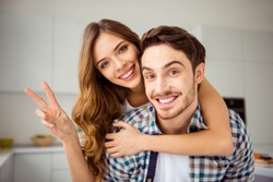 Close up photo pair beautiful funky pair he him his macho she her lady just married romance date satisfied overjoyed piggy back pose hand arm v-sign symbol apartments flat bright white kitchen indoors