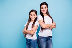 Close up photo pretty two people brown haired mum small little daughter crossed arms self-confidently stand back to back ready win winner family games wear t-shirts isolated bright blue background