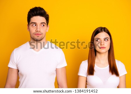 Close up photo two amazing beautiful she her he him his couple standing side by side look each other not smile tell talk speak say wear casual white t-shirts outfit clothes isolated yellow background
