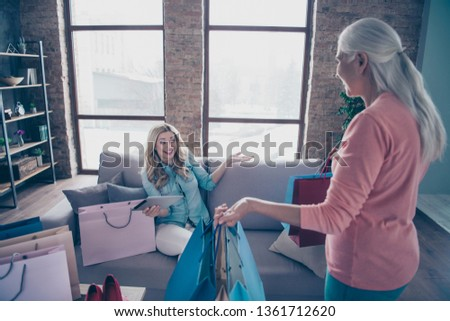 Close up photo two funny beautiful people she her ladies granny granddaughter showroom shop clothes tablet catalogue online lazy buy buyer easy way gifts present sit couch divan sofa house indoors