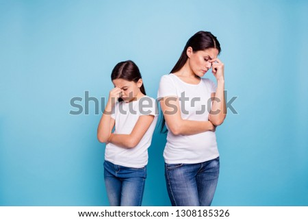Close up photo two people brown haired mum disinterested small little daughter hand on face sick and tired sorry blaming eyes closed wear white t-shirts isolated bright blue background