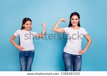 Close up photo two people brown haired mum mom small little daughter hand on biceps who run world girls wear white t-shirts isolated bright blue background #1308185323