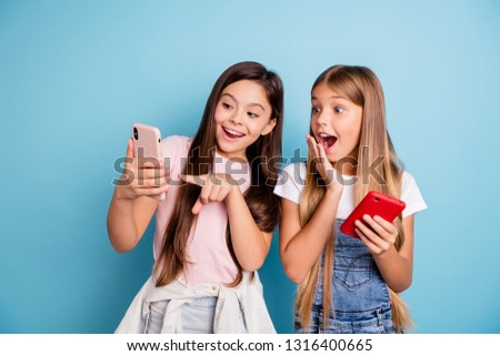 Close up photo two people little she her blond brunette girls long pretty hair telephone point finger to touch screen open mouth wearing casual jeans denim t-shirts isolated blue bright background