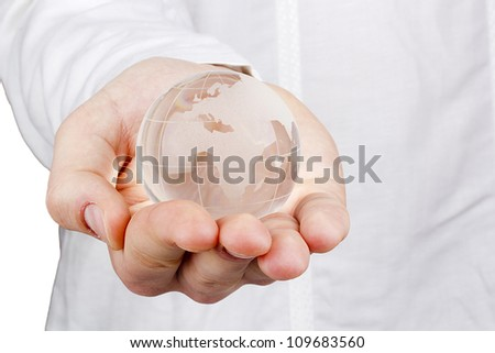 Close-up photograph of a glass globe in a man's hand.