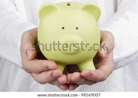 Close-up photograph of a green piggy bank in man's hands.
