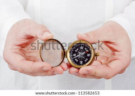 Close-up photograph of a hand holding an old compass.
