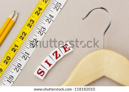 "Close-up photograph of a wooden hanger and measuring tape next to the word ""size"" on a gray background."