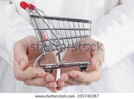 Close-up photograph of man's hands holding a shopping cart.