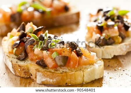 Close up photograph of three tomato and olives bruschetta